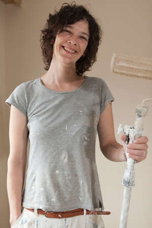 housepainter: Professional working woman holding a paint brush roller at work