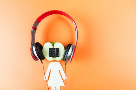 portable audio: Alphanumeric apple with humanoid body listen on blue wooden background