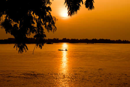 Beautiful sunset in a Mekong River with a fishing boat photo