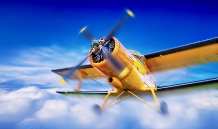 biplane breaks through the clouds Stock Photo