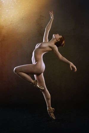 Young ballerina posing against a black background Imagens