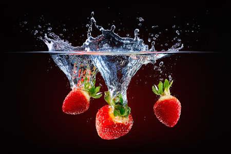 fresh strawberries falling into splashing water Stockfoto
