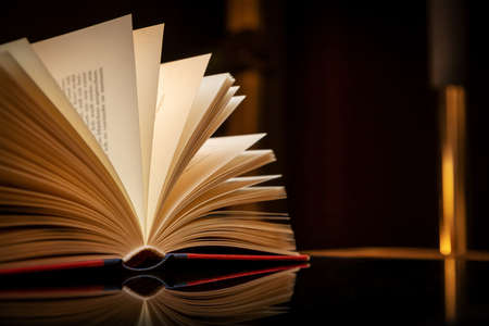 close up of an open book against black Stockfoto