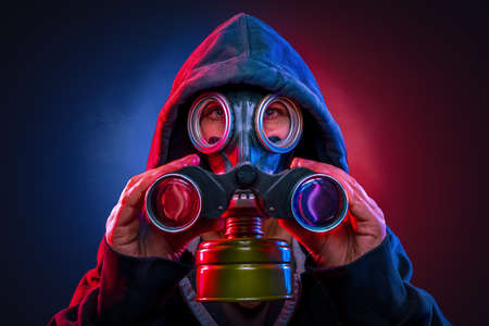 person with a gas mask using a spyglass Stockfoto