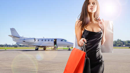young beauty with shopping bags coming from a private jet Stockfoto