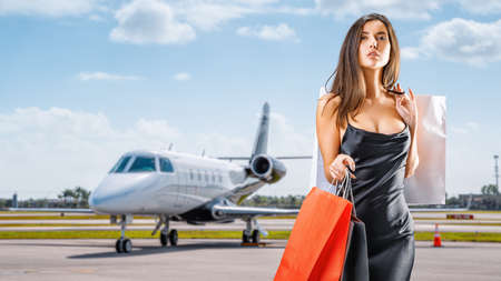 young lady with shopping bags comes from a private jet Stockfoto
