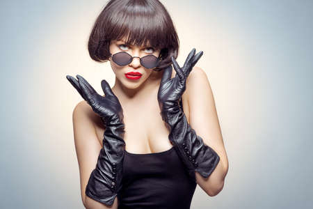 young beauty poses with gloves and sun glasses Stockfoto