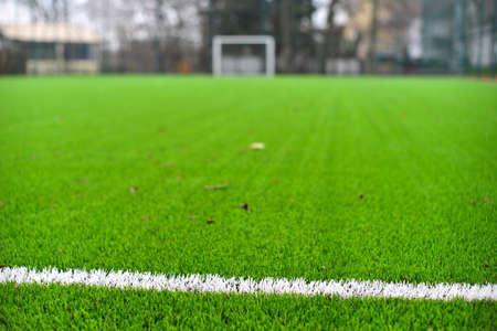 Foto van een groen synthetisch grassportveld met witte lijn hierboven wordt geschoten die van.