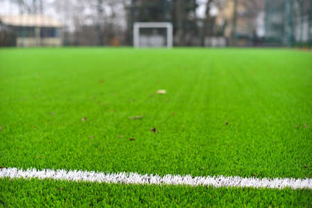 Photo of a green synthetic grass sports field with white line shot from above. Stockfoto