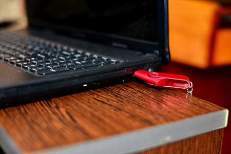 Hand in black glove with red USB flash cards. Hacker copied files from a business computer Stock Photo