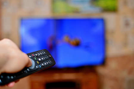 The man with the remote control in hand watching the sports channel and presses the button on the remote control. Remote control in hand closeup. Stockfoto