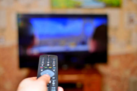 The man with the remote control in hand watching the sports channel and presses the button on the remote control. Remote control in hand closeup. Stock Photo