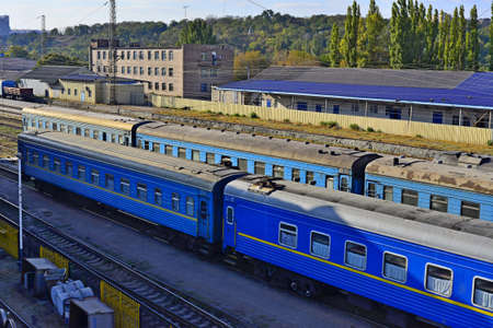 Railway station on the background of blue sky at sunrise with motion blur effect in vintage style. Railroad in Ukraine. Stock Photo