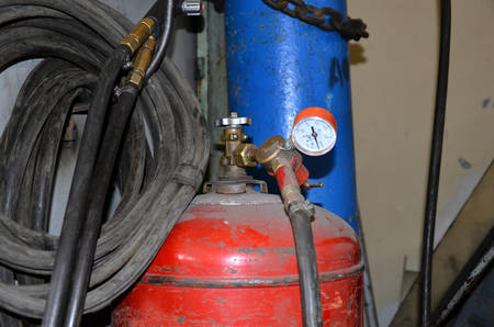 Close-up of a metal gas cylinder with a reducer and a pressure sensor in the background industrial workshop. Close up focus view of welding equipment. Acetylene gas cylinder tank with gauge regulators manometers in the industrial fabric workshop. Stock Photo