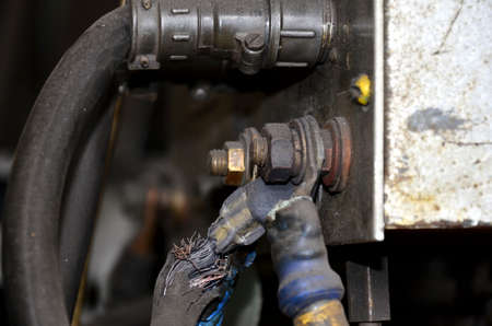 Close-up of a metal gas cylinder with a reducer and a pressure sensor in the background industrial workshop.