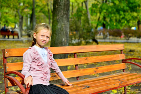 Girl sitting in a bench in the park