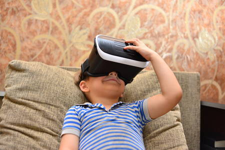 Low angle portrait of little boy wearing VR glasses watching 360 videos and playing augmented reality games at home sitting cross legged on cozy sofa, copy space 版權商用圖片