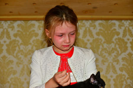the girl is crying, in tears close-up with a black cat a cat in her arms. Beautiful sad little girl crying, on summer background.