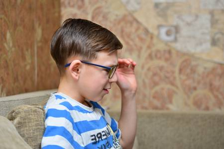 A boy in glasses with striped clothes is sitting on the couch and looking Stock Photo