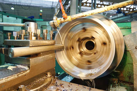Treatment inside the cylinder with a long mechanical chisel on a lathe, with shavings at a production plant close-up.