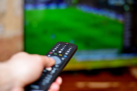 The man switches the sports channel about the football console to the TV in the living room. Stock Photo