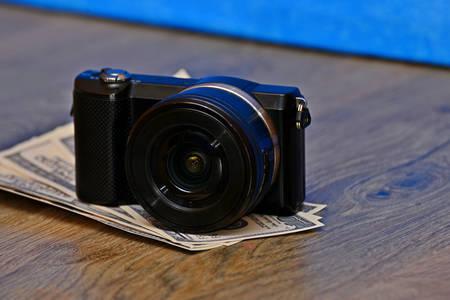 Black camera lies on dollar bills on a dark background