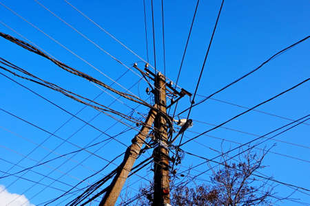 Wooden electric pole with wires on the street in the city against a blue sky. Stock Photo