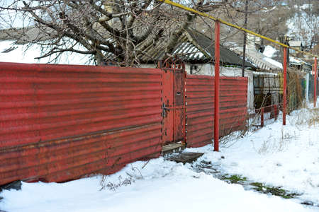 Rusty iron fences with gates on the street, guarding the private territory.