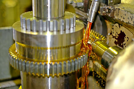 Cogwheel manufacturing on the milling machine with oil cooling. View from the side, the oil is poured onto the cutter and gear part. Stock Photo