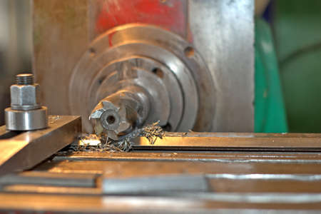 Plate processing by cutting on the milling machine. The detail is clamped by clips on a table. Dry boring by a trailer mill with a smoke and steam. The look with a side, the worker operates manufacturing process at plant.
