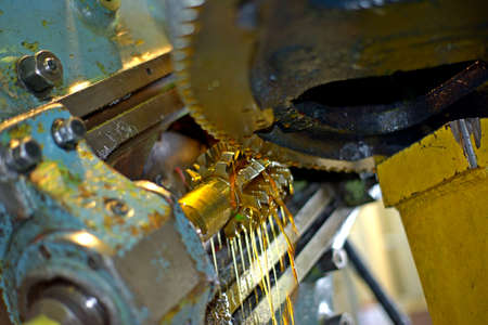 바닥에서 보면 오일이 커터와 기어 부품에 부어집니다. 기계가 가까이 있습니다. 오일 냉각 방식으로 밀링 머신에서 톱니 바퀴 제조. 스톡 콘텐츠 - 97230226