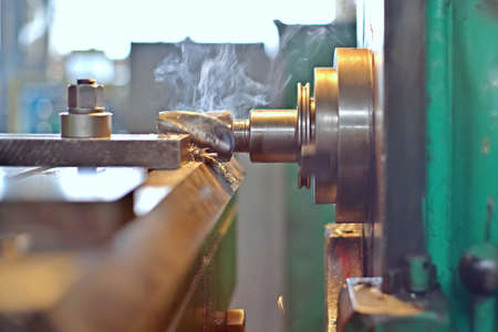 Plate processing by cutting on the milling machine. The detail is clamped by clips on a table. Dry boring by a trailer mill with a smoke and steam. milling machines industrial metalworking cutting process by milling cutter cutting Stock Photo
