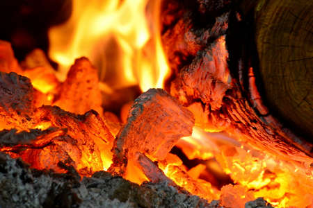 Fire burning from a log in the home fireplace. The firewood burns in the oven and gives heat. Stock Photo