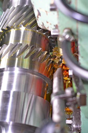 The metal shaft. Clean shiny surface, cutting of teeth splines. Shallow depth of field. Close-up of oil. Stock Photo