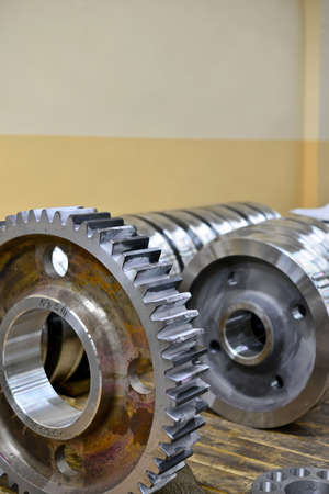 Gear wheel, gear after machining on lathe and CNC milling machine lies on a wooden rack in the shop. Stock Photo