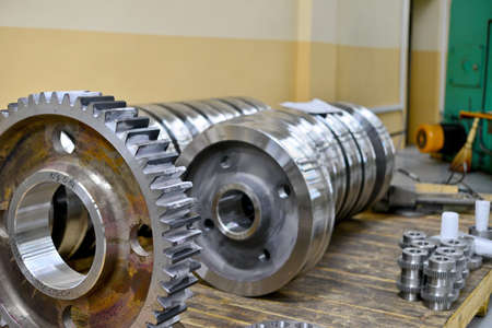Gear wheel, gear after machining on lathe and CNC milling machine lies on a wooden rack in the shop. Stockfoto