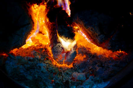 Fire in the fireplace, tongues of flame from a burning log on fire Stock Photo
