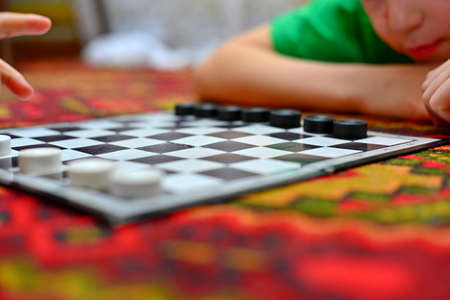 People are playing checkers close-up, the concept of a board game.