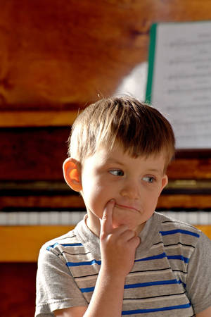 The boy is sitting on a chair near the brown piano in the house