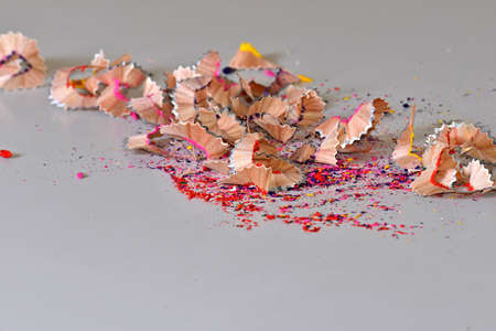 A scrap of colored pencils is laid out on a white background. Creative idea for the background texture.