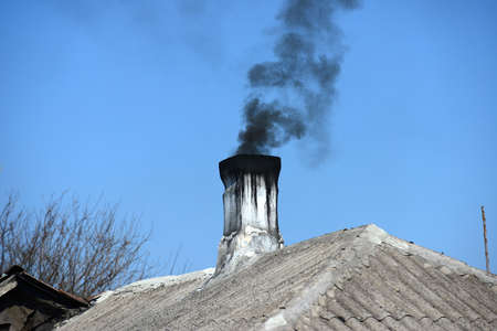 A pipe with black smoke on the roof of a residential building