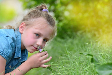Girl in blue clothes sniffing a flower in a field in nature and looking at the camera