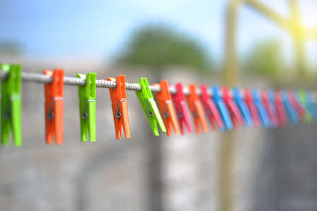 Color clothespins hang on the clothesline. laundry hook, colorful, pegs, rope ,outside, sun ,green, summer decorations, village, blue, sky , yellow ,red ,pins ,pink ,over