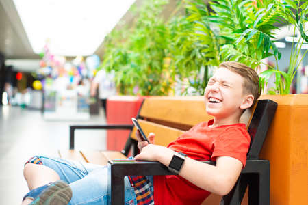 Boy with a smartphone on the bench