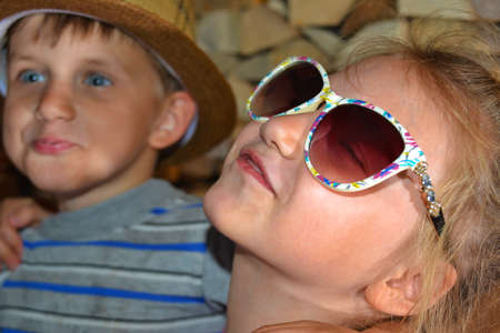 Toned picture of a girl in sunglasses, hugs her younger brother.