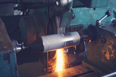 Grinding the shaft on the machine with sparks and cooling, at different angles