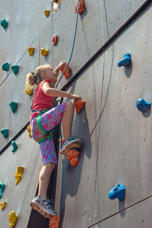 The girl is blonde, climbs to the top on an artificial rock with the help of a safety rope, is engaged in rock-climbing Stock Photo