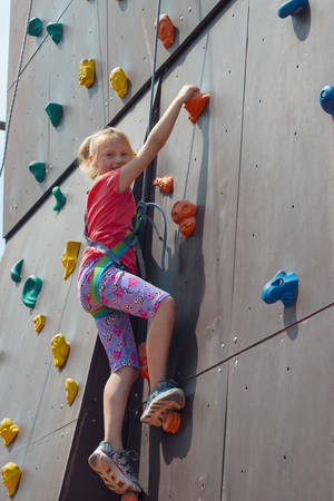 Joyful and happy girl blonde, climbs to the top on an artificial rock and looks into the camera with a safety rope, is engaged in rock climbing Stock Photo