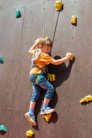 A frightened little boy, wants to climb up on an artificial rock with a safety rope, is engaged in rock climbing