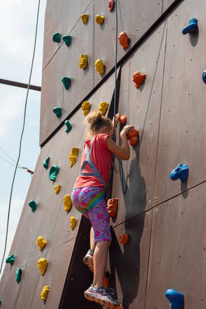 Joyful and happy girl blonde, climbs to the top on an artificial rock and looks into the camera with a safety rope, is engaged in rock climbing 스톡 콘텐츠